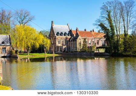 Bruges, Belgium - April 10, 2016: Spring morning in Bruges, Belgium at Lake of Love or Minnewater, medieval houses against blue sky