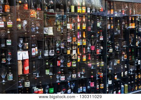 Bruges, Belgium - April 10, 2016: Beer Wall in Bruges Bar with different bottles and glasses