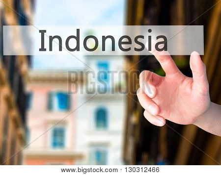 Indonesia  - Hand Pressing A Button On Blurred Background Concept On Visual Screen.