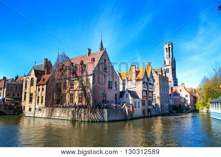 Bruges, Belgium - April 10, 2016: Scenic cityscape with medieval houses, tower Belfort and canal in Bruges, Belgium