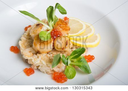 Seafood risotto served wtih scallop and red caviar