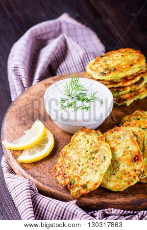 Zucchini Fritters With Herbs And Feta On The Wooden Board