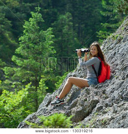 photo of young beautiful girl climbing the rock