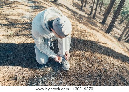 Sporty young man tying shoelaces in the forest outdoor