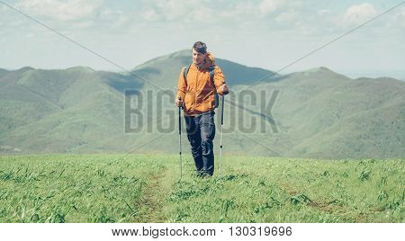 Hiker young man with backpack and trekking poles walking in the mountains in summer outdoor front view