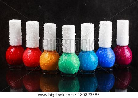 Group of bright nail polishes sorted like a rainbow. Bottles with water drops are standing in a row on black stone background with reflection. Beauty concept.