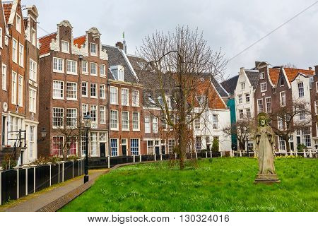 Amsterdam, Netherlands - March 31, 2016: Begijnhof courtyard with Jesus statue and garden surrounded by historic houses in Amsterdam, Netherlands
