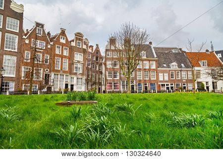 Amsterdam, Netherlands - March 31 2016: Colorful view of Begijnhof courtyard with historic Holland houses in Amsterdam, Netherlands