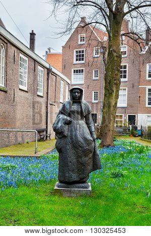 Amsterdam, Netherlands - March 31, 2016: Begijnhof courtyard with nun statue and garden surrounded by historic houses in Amsterdam, Netherlands