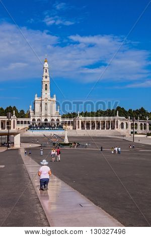 FATIMA, PORTUGAL - SEPTEMBER 9, 2011: The area in front of the Catholic cathedral with tourists and believers. Religious woman in hat kneeling on a specially built track