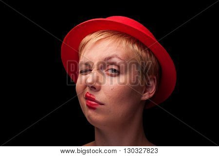 horizontal front view portrait of a young blonde woman with red hat making a face on black background