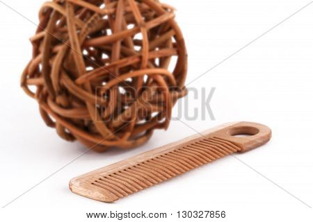 horizontal front view of a wooden comb next to a ball of twisted brown wood branches isolated on white background