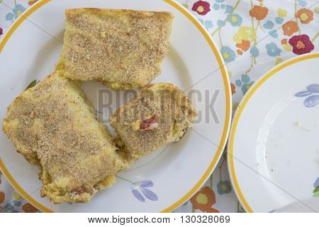 wedge of pie of potatoes stuffed with ham and salami
