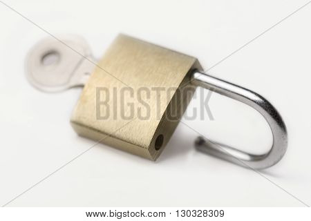 Horizontal side view of an open lock with key isolated on white background