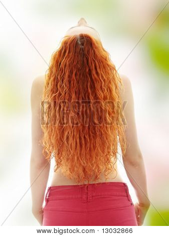 Rear view of the young female with beauty curly long hairs