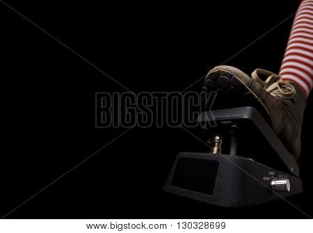 Horizontal side view of a show pressing a rock music pedal on black background