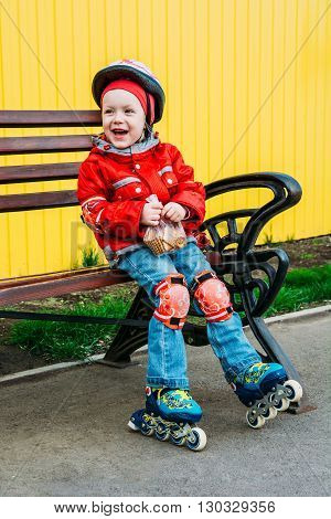 Little Girl In Roller Skates Sitting On Bench