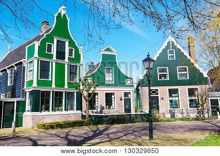 Zaanse schans, Netherlands - April 1, 2016: Zaanse Schans traditional village North Holland, green houses against blue cloudy sky