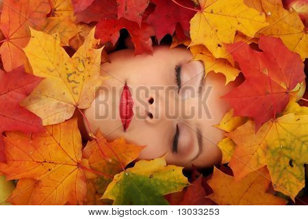 Close-up of a woman face in autumn leafs