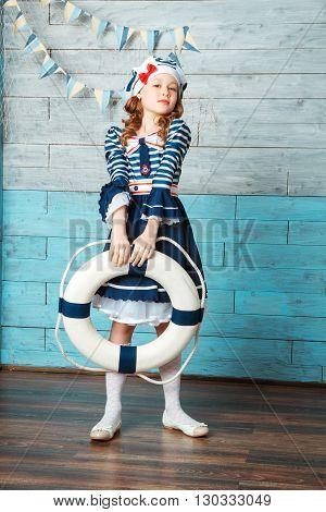 little girl holding a life preserver vest