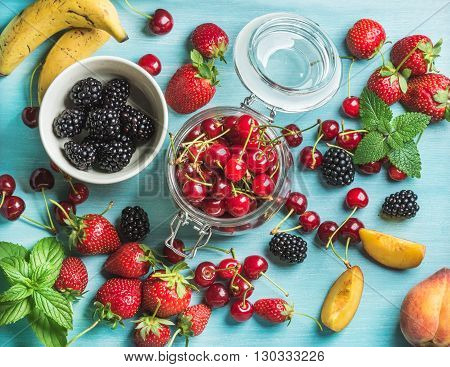 Healthy summer fruit variety. Sweet cherries, strawberries, blackberries, peaches, bananas and mint leaves on blue backdrop. Top view, copy space