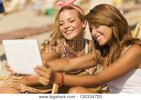 Two beautiful young girls lying on a sunbed on the beach taking a selfie with a tablet computer