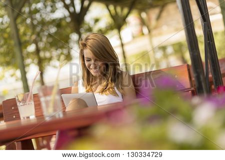 Beautiful brunette sitting in an outdoor cafe reading an e-book on her tablet computer