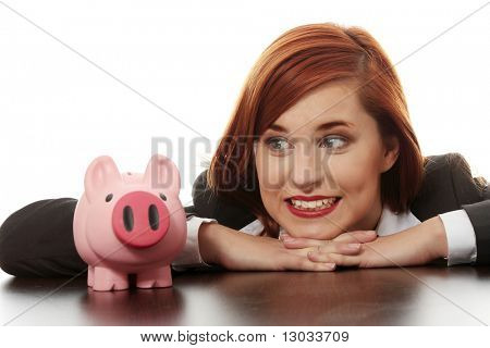 Young Business Woman looking auf Rosa Sparschwein, isolated on white background