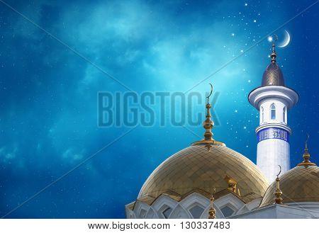 Ramadan Kareem background.Crescent moon at a top of a mosque