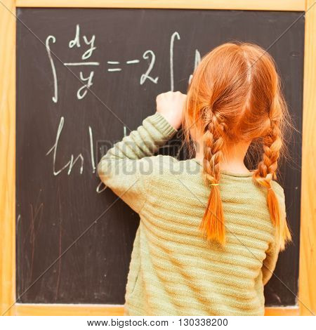 Back to school concept. Little girl writing formulas on blackboard. Square image