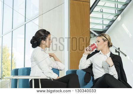 Two business colleagues sitting in a modern office building hallway on a coffee break