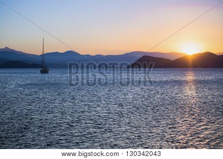 Harbor in tropical sea with boats at sunset light