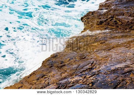 Nature blue turquoise sea vacation background with foam and waves on stone beach shore, close up