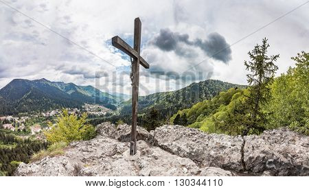 Panoramic view of Romanian town Baile Tusnad in Carpathian mountains from cliff with large wooden cross