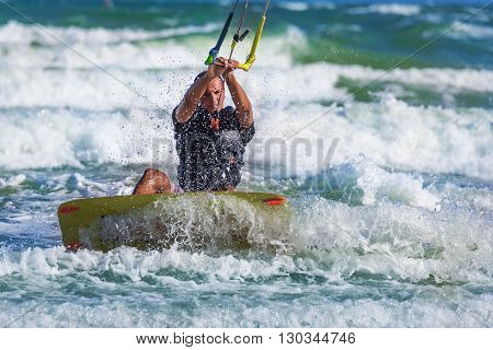 Athletic Man Riding On Kite Surf Board At Sea Waves