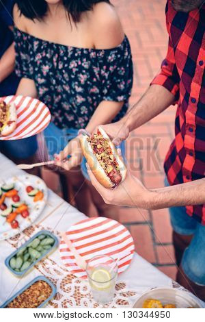 Close up of unrecognizable young man holding an american hot dog in a outdoors summer barbecue with his friends