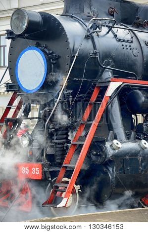 LVIV UKRAINE - DECEMBER 2015: Old Soviet vintage black retro train L-3535 at the railway station in Lviv produces steam from the pipes