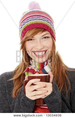 Young woman with winter cap drinking something hot, isolated on white