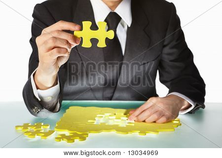 Businessman Trying To Finish The Puzzle