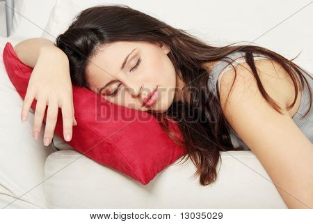 Beautiful young woman sleeping on sofa.