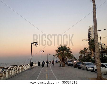 The famous seaside Corniche on sunset, Beirut, Lebanon. Beirut, Lebanon -  December 24, 2015: People take their sunset walk on the famous Corniche (seaside promenade) in Beirut, Lebanon