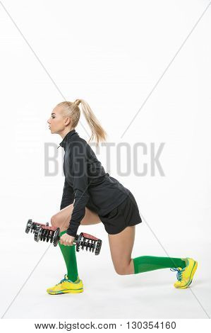 Pretty blonde with dumbbells in her hands does exercise in the studio on the white background. She dressed in the multicolored sportswear: yellow-blue sneakers, green knee socks, black shorts and black hoody. She stands sideways to the camera. Vertical.