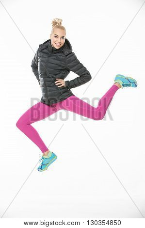 Smiling young blonde girl in the sportswear jumps on the white background in the studio. She wears cyan-yellow sneakers, pink pants and black jacket. She holds her hands on her waist. She looks into the camera. Vertical.