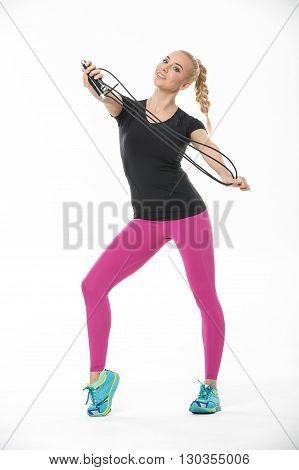 Athletic smiling blonde in the sportswear stands on the white background in the studio. She wears cyan-yellow sneakers, pink pants and black t-shirt. She pulls a skipping rope with her raised hands. She looks into the camera. Vertical.