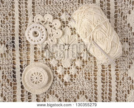 Vintage background with Irish cotton lace crochet flowers. Crochet doilies, crochet pattern coasters and hook background. Handmade lace. Christmas or Valentine's day background.