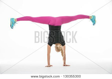 Incredible blonde gymnast girl in the sportswear stands upside down on her hands on the white background in the studio. Shoot from the back. She wears cyan-yellow sneakers, pink pants and black t-shirt. She stretches her legs to the sides. She has a plait