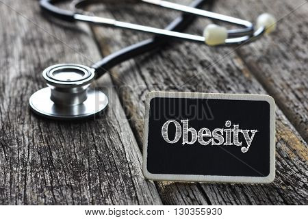 Medical Concept-Obesity word written on blackboard with Stethoscope on wood background
