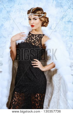 Gorgeous young woman wearing evening dress and beautiful furs. Luxury, rich lifestyle. Jewellery. Fashion shot.