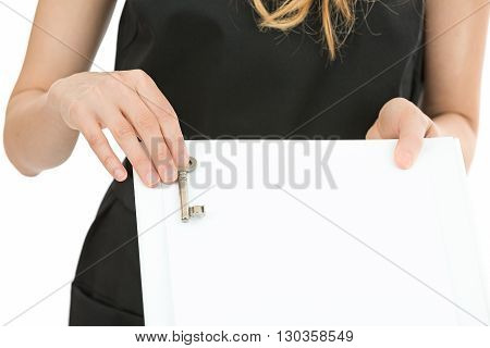 Business woman showing a key for a sale with an agreement. Isolated on white bakground.