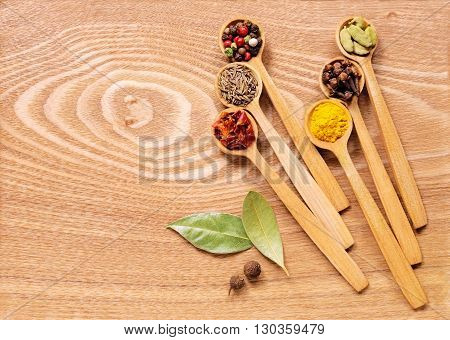 A set of several spices in wooden spoons on wooden table. In the set has a mixture of different peppers, allspice, turmeric, clove, cumin, cardamom, paprika, Bay leaf. Top view.